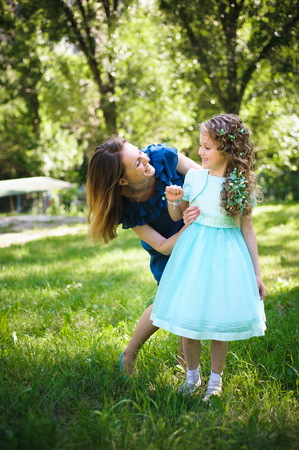Happy mother and daughter together in a summer park outdoors.