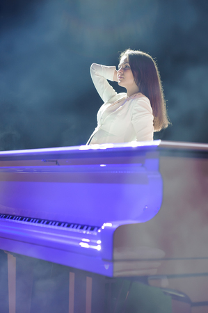 The woman with white piano. Beautiful pianist on the stage near the piano. Standard-Bild - 122371812