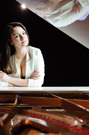 The woman with white piano. Beautiful pianist on the stage near the piano.