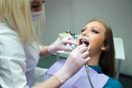 Doctor in uniform checking up female patients teeth in dental clinic 写真素材 - 122324915