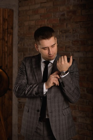 Elegant businessman correcting his cufflinks and sleeve