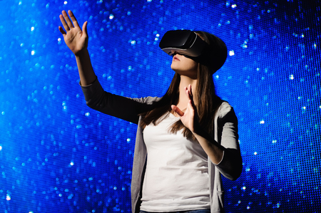 A beautiful girl wearing a virtual reality device, standing on the background of the sky. 免版税图像