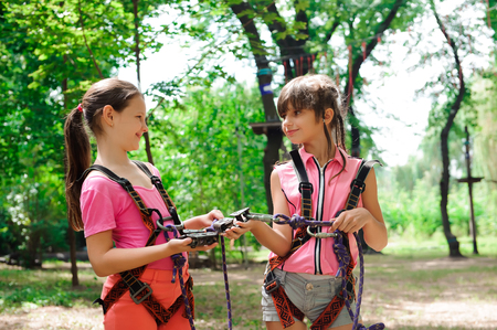 Adventure climbing high wire park - hiking in the rope park two sisters teenagers in safety equipment.