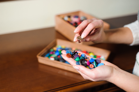 colorful sewing buttons in the hands.