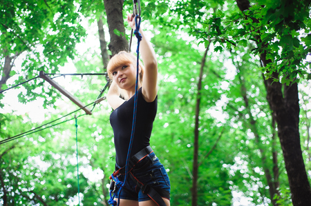 Hiking in the rope park beautiful sports girl Stock Photo