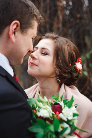 Portrait of happy newlyweds in autumn nature. Happy bride and groom embracing and kissing