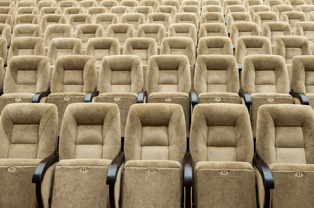 Empty auditorium with beige chairs, theatre or conference hall.