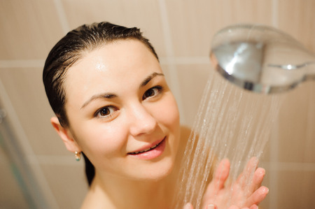 beautiful naked young woman smiling while taking shower in bathroom