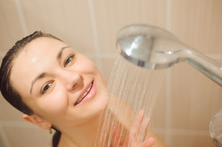 beautiful naked young woman smiling while taking shower in bathroom.