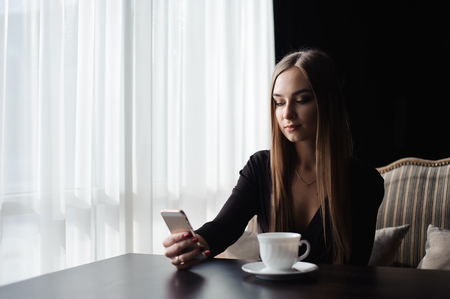 Portrait of young businesswoman use mobile phone while sitting in comfortable coffee shop during work break.