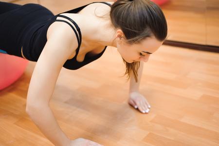 felice ragazza atletica carina, esegui esercizio e sorridi, nel palazzetto dello sport. Archivio Fotografico