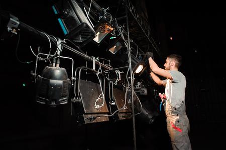 El trabajador del escenario enciende las luces