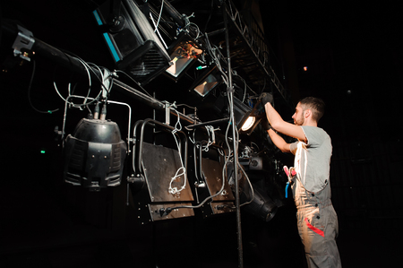 Pracownik sceny ustawia światła