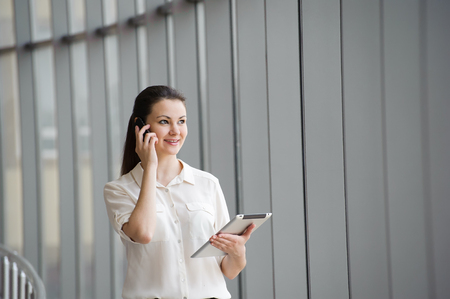 Young businesswoman talking on mobile phone and working on tablet while standing by window in office. Beautiful young female model in bright office
