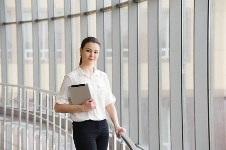 Joven empresaria de pie junto a la ventana en la oficina. Modelo de mujer joven hermosa en la oficina. Foto de archivo