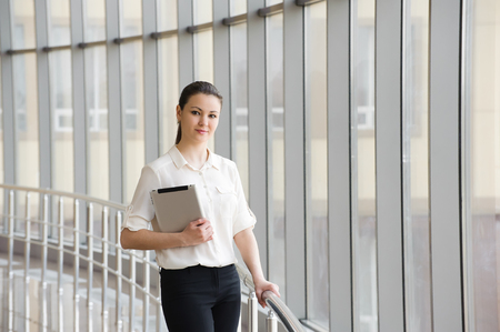 Young businesswoman standing by window in office. Beautiful young female model in office. Imagens