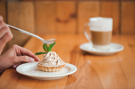 Woman eating a cake of cottage cheese in a ceramic plate with a spoon on a wooden table. 版權商用圖片