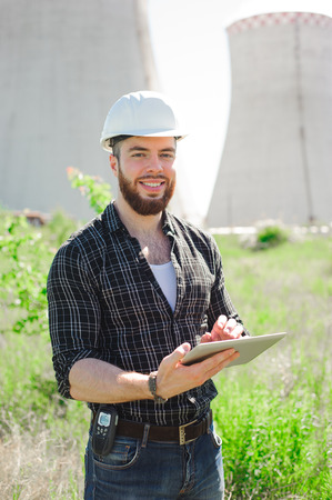 Smiling engineer using a tablet in a facility. Imagens