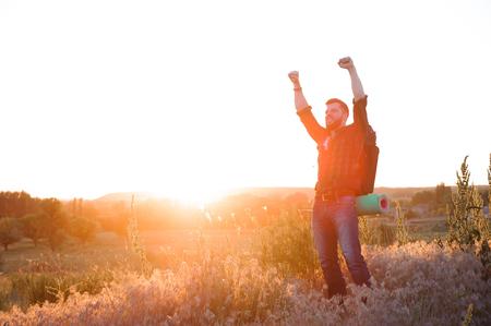 Junger Mann betrachtet Sonnenuntergang. Reisender mit Rucksack Standard-Bild