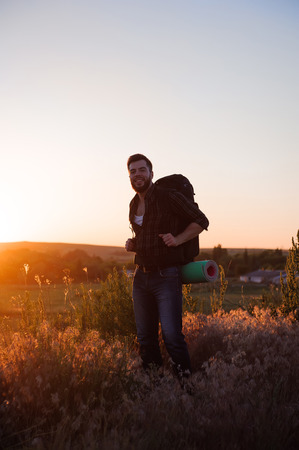 Young man is looking at sunset. Traveller with backpack