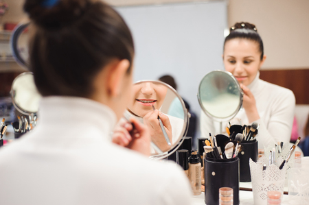 School of makeup. Make up artist doing professional make up of young woman. Beauty shcool Stock Photo