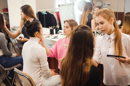 Three professional make-up artists work with beautiful young women. School of professional make-up.