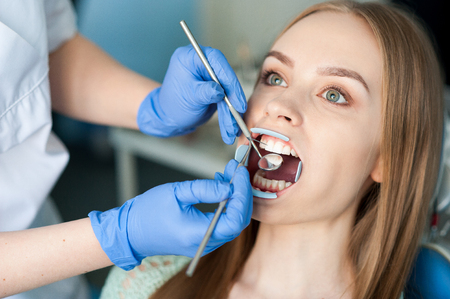 Dentist examining a patients teeth in the dental clinic. 写真素材
