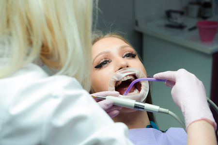 female doctor in uniform checking up female patients teeth in dental clinic. 写真素材