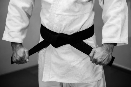 Aikido black belt on white kimono in a sport jum