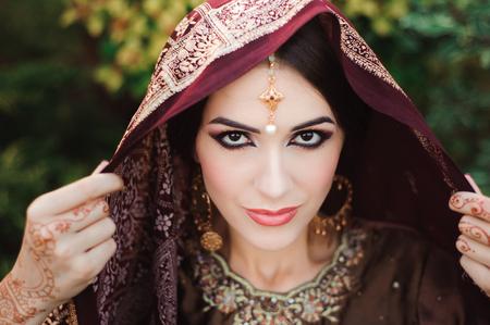 Portrait of beautiful indian girl . Young hindu woman model with tatoo mehndi and kundan jewelry