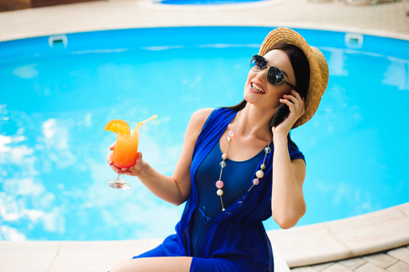 Beautiful young woman with phone near swimming pool 写真素材