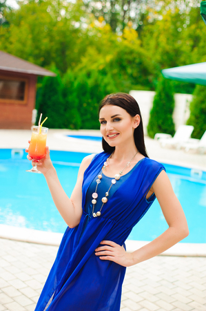 Enjoying summer. Beautiful young woman drinking cocktail while relaxing near the pool.