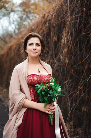 portrait of a beautiful bride in a red dress with a wedding bouquet in a hand 版權商用圖片