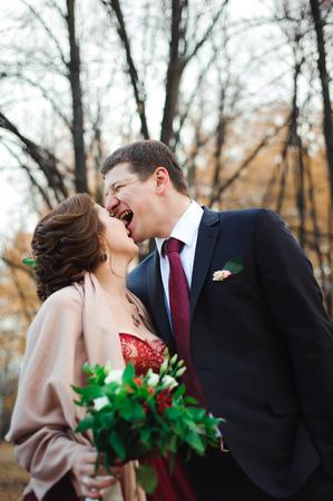 glückliche Braut und Bräutigam, die im Herbstwald gehen