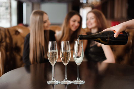 Man fills glasses of champagne for three beautiful young women in restaurant Stockfoto
