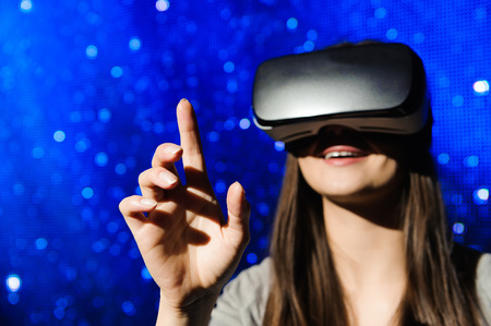 a beautiful girl wearing a virtual reality device, standing on the background of the sky. Stock Photo