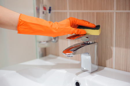 Hands in gloves with rubber cleaning bath faucet