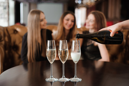 Man fills glasses of champagne for three beautiful young women in restaurant. Stockfoto