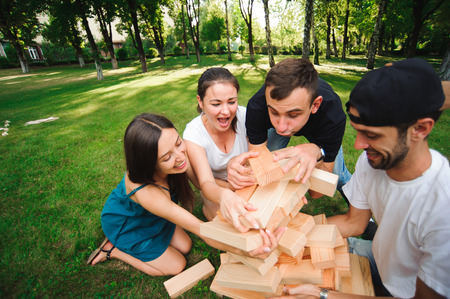 Friends playing board game outdoors. Group game of physical skill with big blocks Stockfoto