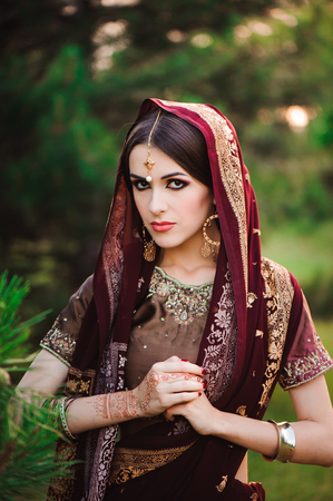 Beautiful young caucasian woman in traditional indian clothing sari with bridal makeup and jewelry and henna tattoo on hands Stock Photo