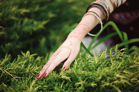 Woman Hands with black mehndi tattoo. Hands of Indian bride girl with black henna tattoos. Fashion. India Stock Photo