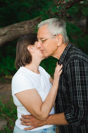 Romantic senior couple walk through the woods
