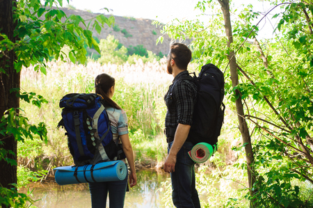 adventure, travel, tourism, hike and people concept - smiling couple with backpacks outdoors. 版權商用圖片