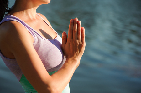 Close up portrait of attractive woman in meditating position on wooden log at the lake. Young girl doing yoga.