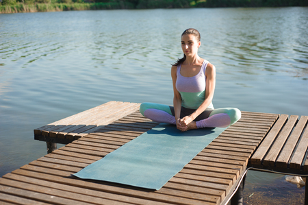 Woman Yoga - relax in nature. Caucasian woman yoga on the bridge, meditating in yoga pose at a mountain stream.