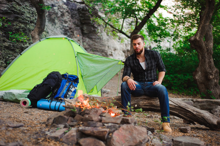 Traveler man relaxing, looking at the fire and dreaming at camping tent outdoors on nature 写真素材