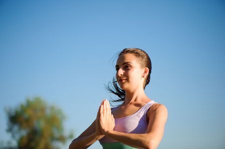 Close up of young woman doing yoga in the park with sunset. 写真素材