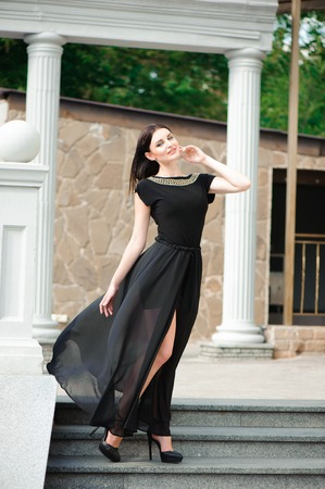young woman in a long black dress down the stairs.