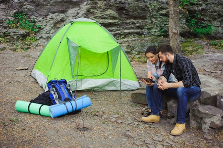 Couple camping in the mountains, the tent, two backpacks near a tourist track in mountains