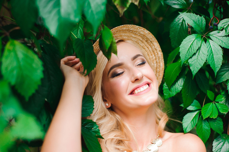 Woman in hat and summer clothes posing near the green leaves